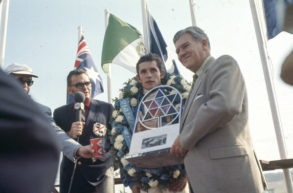 Race winner Jacky Ickx is presented with his trophy on the podium. ABC World of Sport commentator Chris Economaki stands to Ickx's right.