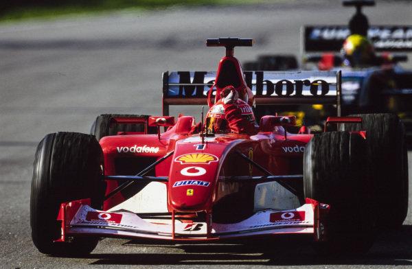 Michael Schumacher, Ferrari F2002, celebrates victory in front of Mark Webber, Minardi PS02 Asiatech.