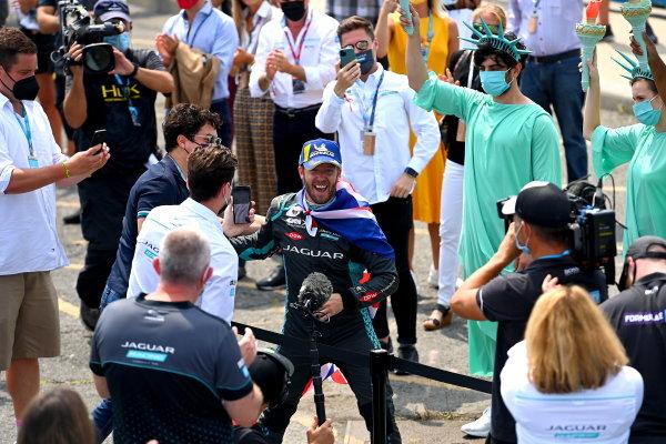Sam Bird (GBR), Jaguar Racing, 1st position, celebrates in Parc Ferme with a Union flag cape