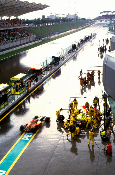 2001 Malaysian Grand Prix.Sepang, Kuala Lumpur, Malaysia. 16-18 March 2001.Jos Verstappen (Arrows A22 Asiatech) enters the pits as Jarno Trulli (Jordan EJ11 Honda) is midway through his pitstop.World Copyright - Martyn Elford/LAT Photographic ref:35mm Image A21