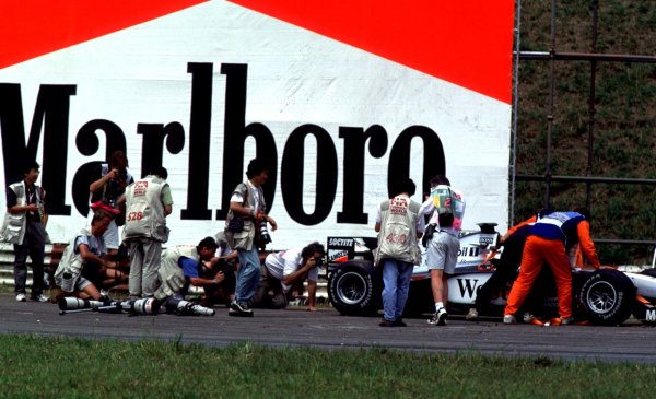 1998 Brazilian Grand Prix.Interlagos, Sao Paulo, Brazil.27-29 March 1998.Photographers crowd round a stranded McLaren MP4/13 Mercedes-Benz out on the track.World Copyright - LAT Photographic