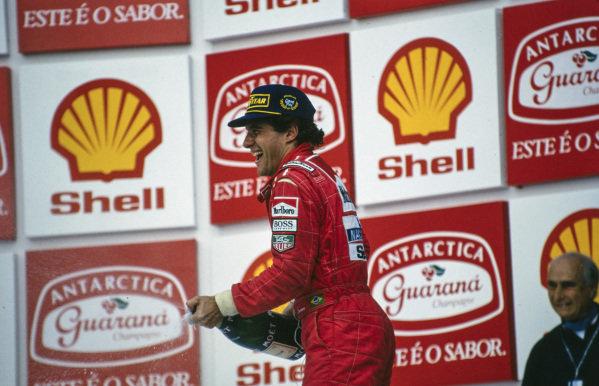 Ayrton Senna, 1st position, celebrates on the podium. Juan Manuel Fangio can be seen stood beside.
