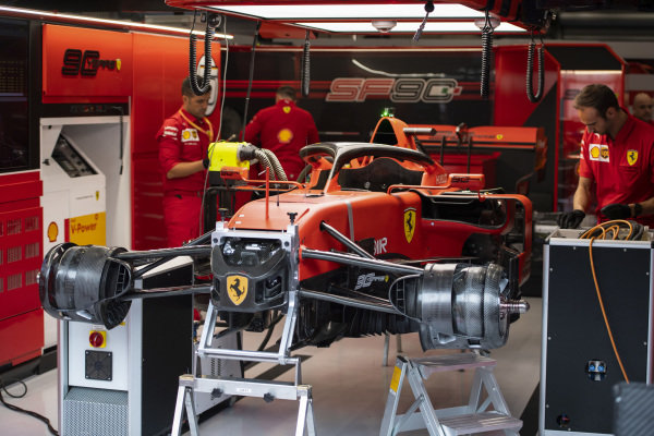 Mechanics work on a Ferrari SF90 in the team's garage