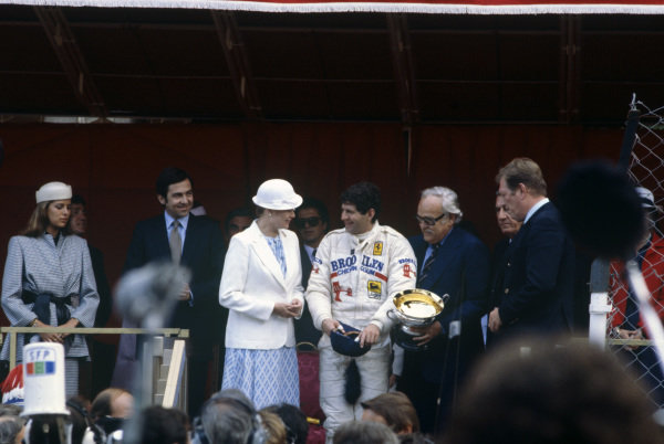 Jody Scheckter celebrates victory on the podium with Princess Grace and Prince Rainier III.