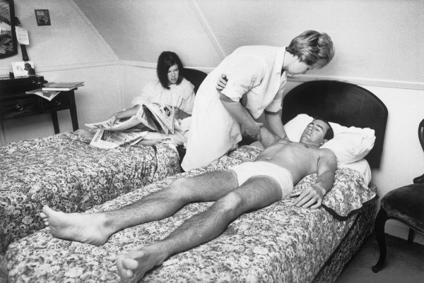 Brands Hatch, Kent, Great Britain. 16 July 1966.Jackie Stewart (B.R M. P261), has massage treatment by an ostepath, while wife Helen, catches up with the news. This is Stewart's first race since his accident at the Belgian Grand Prix at Spa where he suffered a broken collarbone and ribs, portrait. World Copyright: David Hudson/LAT Photographic.Ref:  DH - 66GB - Neg7-7A.