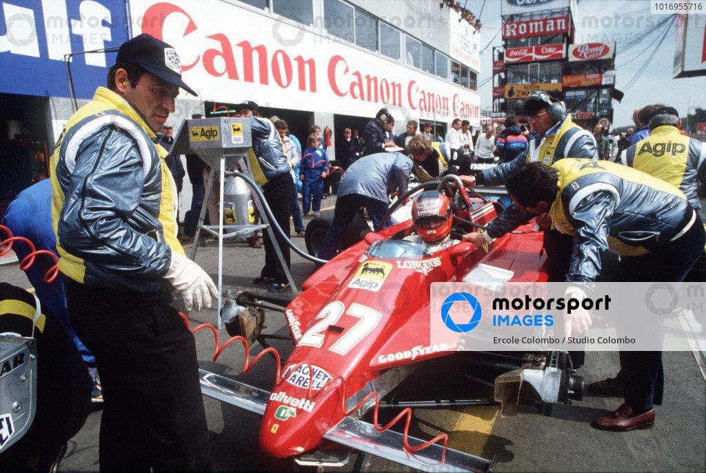 Mechanics work on Gilles Villeneuve's Ferrari 126C2 as he sits in the car.