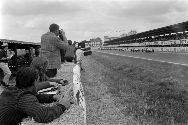 Timekeepers watch the action from beside the track. Mechanics hold out pit boards from the side of the track.