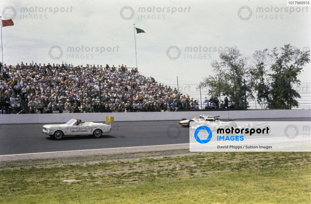 Jim Clark, Lotus 34 Ford, Bobby Marshman, Lindsey Hopkins, Lotus 34 Ford, and Roger Ward, Bob Wilke, Watson Ford, form up the front row behind the Ford Mustang pace car before the race.