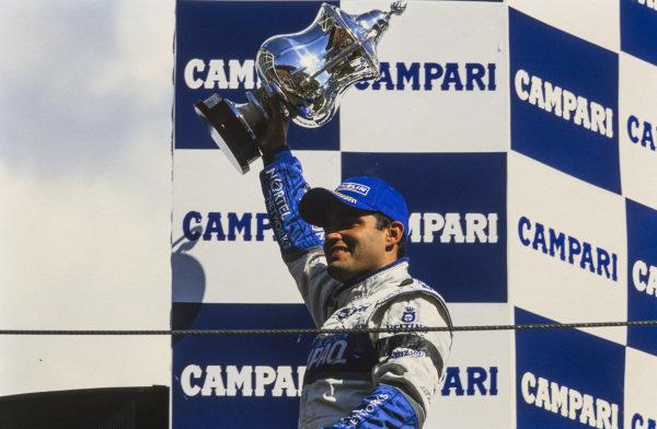 Juan Pablo Montoya, 1st position, celebrates his maiden victory on the podium.