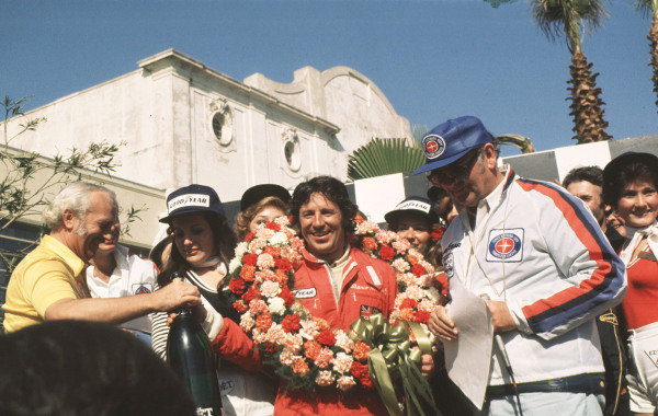 1977 United States Grand Prix West.Long Beach, California, USA. 1-3 April 1977.Mario Andretti (Team Lotus) celebrates his 1st position on the podium with team boss Colin Chapman. Ref-77 LB 08.World Copyright - LAT Photographic