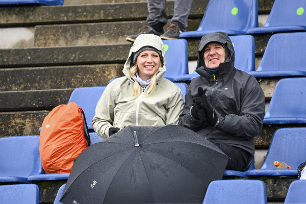 Fans sit out in the rain