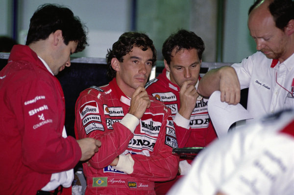 Ayrton Senna and Gerhard Berger with engineers James Robinson and Steve Hallam in the McLaren garage.