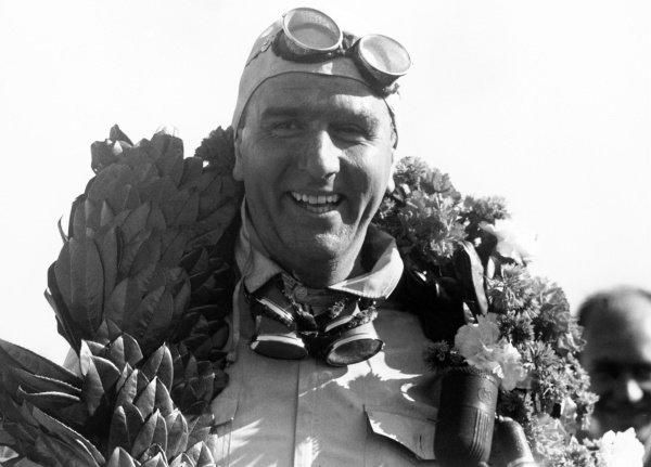 1950 British Grand Prix. Silverstone, Great Britain. 13 May 1950. Giuseppe Farina, Alfa Romeo 158, 1st position, portrait, helmet, podium. World Copyright: LAT Photographic Ref: 3734A/34