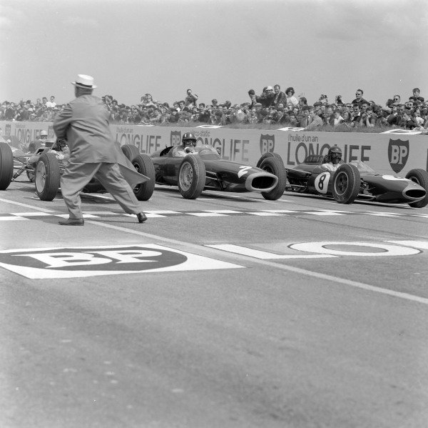 The front row prepared for the start of the race as an official runs away from the circuit. Jim Clark, Lotus 25 Climax, is alongside Graham Hill, BRM P61, and Dan Gurney, Brabham BT7 Climax.