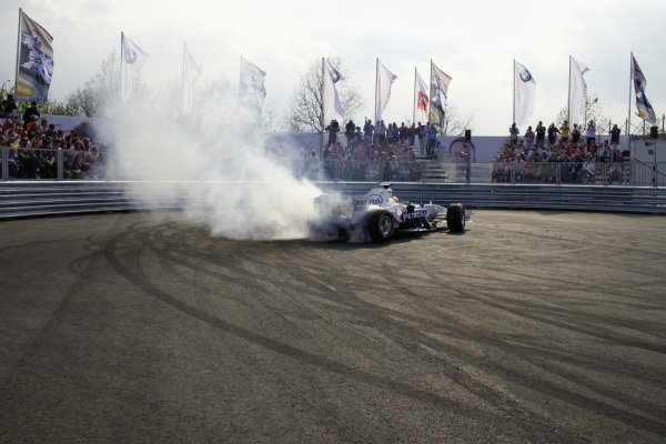 Fans watch as BMW Sauber F1 test driver Dirk Müller performs a donut during a demo run.