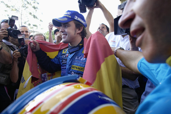 World Champion Fernando Alonso celebrating with a Spanish flag.