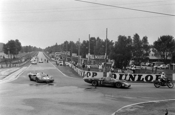 A policeman on a motorbike leads Arturo Merzario / Clay Regazzoni, SpA Ferrari SEFAC, Ferrari 512 S, and Jacky Ickx / Peter Schetty, SpA Ferrari SEFAC, Ferrari 512 S, the wrong way into the corner.