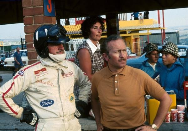 The reigning World Champion Graham Hill (GBR) watches an event further up the pit lane with the Lotus Team Manager Colin Chapman (GBR) and his faithful timekeeper, wife Bette. South African Grand Prix, Kyalami, 1 March 1969.   BEST IMAGE