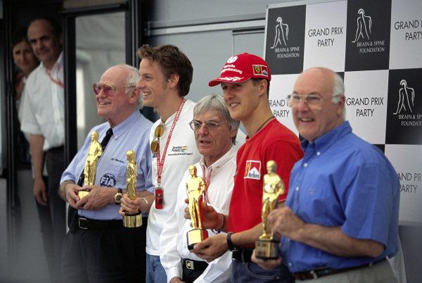 Professor Sid Watkins, Jenson Button, Benetton, Michael Schumacher, Ferrari, and commentator Murray Walker pick up their 'Bernie' awards, which are presented by Bernie Ecclestone (middle).
