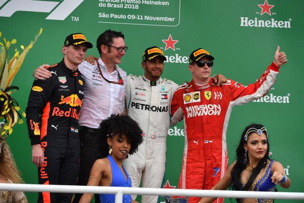 (L až R): Max Verstappen, Red Bull Racing, Andy Shovlin, hlavný inžinier Mercedes-AMG F1, Lewis Hamilton, Mercedes AMG F1 a Kimi Raikkonen, Ferrari oslavujú na pódiu s dievčatami samby