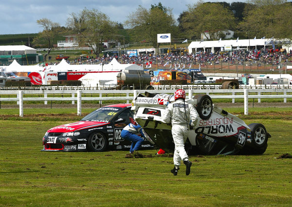 V8 SUPERCAR drivers race to help Jason Richards after he rolled his Holden Commodre at the end of the first practice session at Pukekohe raceway 40km south of Auckland, New Zealand 07/11/03.Copyright - LAT