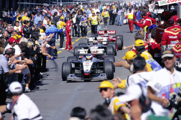 Mika Hakkinen, McLaren MP4-13 Mercedes, teammate David Coulthard and Heinz-Harald Frentzen, Williams FW20 Mechachrome, in pitlane at the end of the race.