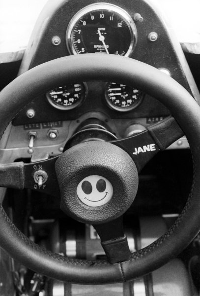 The steering wheel of an F1 car with a smiley face and a dedication to Jane.