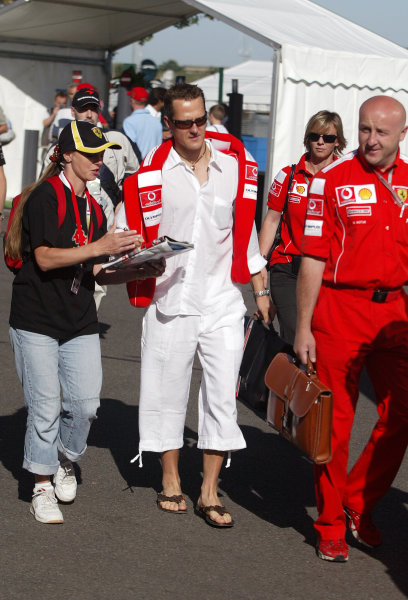 2004 French Grand Prix - Sunday Race,Magny Cours, France. 04th July 2004 Michael Schumacher, Ferrari F2004, is pursued by an autograph hunter as he arrives at the circuit.World Copyright: Steve Etherington/LAT Photographic ref: Digital Image Only