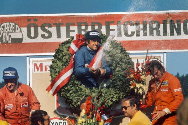 1974 Austrian Grand Prix  Osterreichring, Austria. 16-18th August 1974.  Carlos Reutemann, Brabham, 1st position, celebrates on the podium with Denny Hulme, McLaren, 2nd position and James Hunt, Hesketh, 3rd position.  Ref: 74AUT02. World Copyright: LAT Photographic