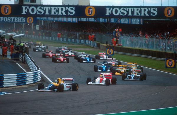 1993 British Grand Prix. Silverstone, England. 9-11 July 1993. Damon Hill (Williams FW15C Renault) leads Ayrton Senna (McLaren MP4/8 Ford), Alain Prost (Williams FW15C Renault), Michael Schumacher (Benetton B193B Ford), Martin Brundle (Ligier JS39 Renault), Riccardo Patrese (Benetton B193B Ford) and Johnny Herbert (Lotus 107B Ford) at the start.  Ref-93 GB 11. World Copyright - LAT Photographic