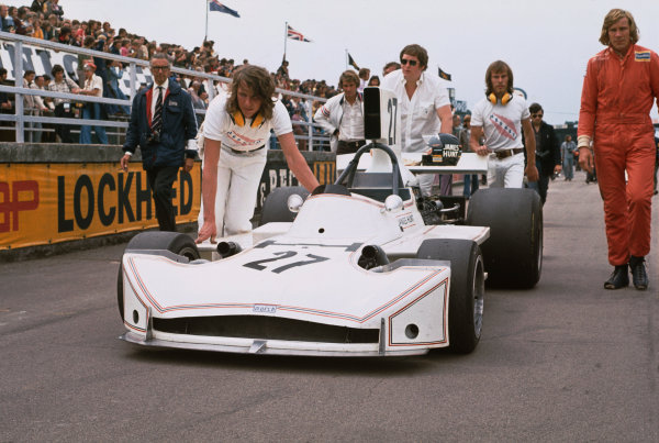 Silverstone, England. 14th July 1973.Anthony (Bubbles) Horsley and Harvey Postlethwaite and James Hunt along with two Hesketh mechanics, walk the March 731-Ford, onto the grid at the start, portrait.World Copyright: LAT Photographic.Ref:  Colour Transparency.