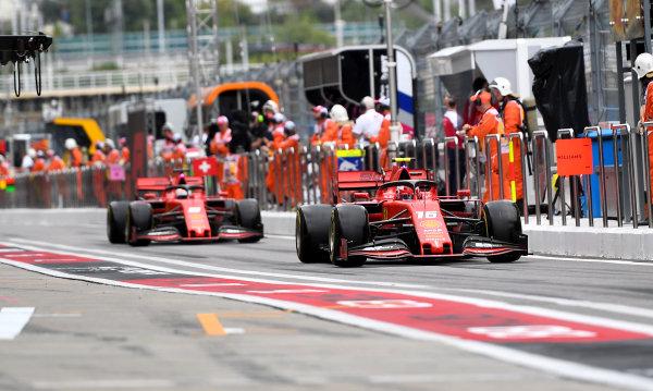 Charles Leclerc, Ferrari SF90, leads Sebastian Vettel, Ferrari SF90, in the pit lane