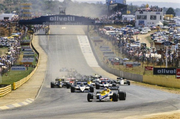 Nigel Mansell, Williams FW10 Honda, leads Nelson Piquet, Brabham BT54 BMW, Marc Surer, Brabham BT54 BMW, Elio de Angelis, Lotus 97T Renault, Ayrton Senna, Lotus 97T Renault, kicking up dust and Keke Rosberg, Williams FW10 Honda, into the first corner at the start.