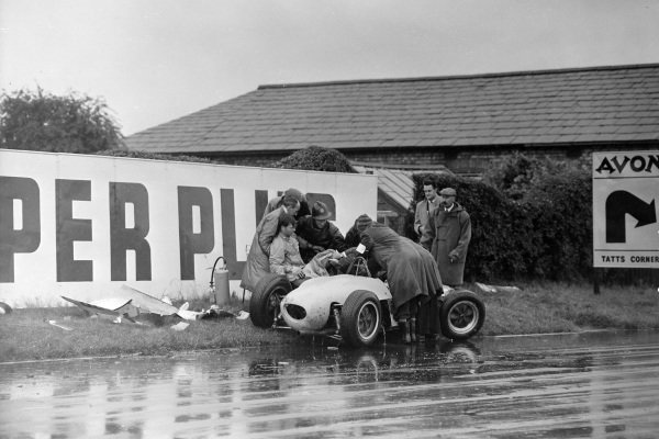 Henry Taylor, Lotus 18/21 Climax, crashes at the Melling Crossing before slammed into an advertising hoarding. Here he is helped out of his car by marshals and firemen.