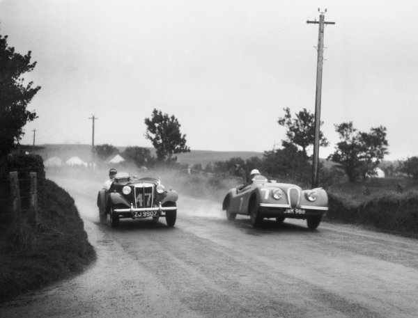 Dundrod, Northern Ireland. 16th September 1950. Stirling Moss (Jaguar XK120), 1st position, passes T. Flack (MG TD), 23rd position, action. World Copyright: LAT Photographic Ref: Autocar Glass Plate C27789