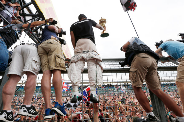 Silverstone Circuit, Northamptonshire, England. Sunday 5 July 2015. Lewis Hamilton, Mercedes AMG, 1st Position, shows his trophy to the crowds. World Copyright: Alastair Staley/LAT Photographic ref: Digital Image _79P4019