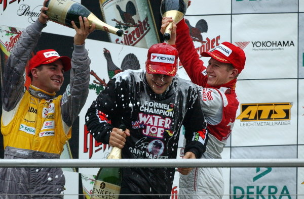Race winner and 2002 champion Gary Paffett (GBR), Team Rosberg, centre, gets a champagne shower from second placed Timo Glock (GER), left, Opel Team KMS,  and third placed Ryan Briscoe (AUS), right, Prema Powerteam.German Formula 3 Championship, Rd10, Hockenheim, Germany, 5-6 October 2002.DIGITAL IMAGE