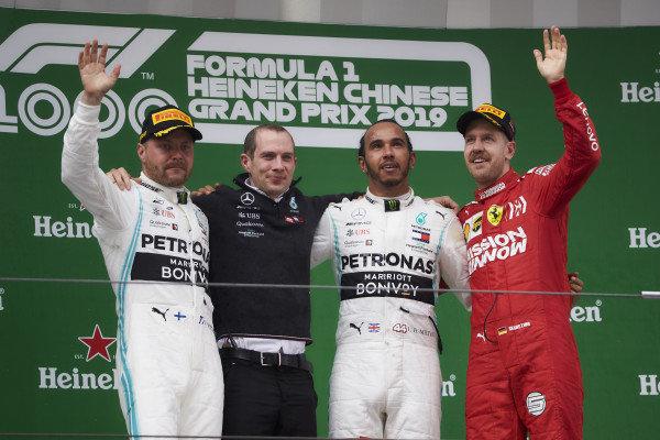 Valtteri Bottas, Mercedes AMG F1, 2nd position, the Mercedes Constructors trophy delegate, Lewis Hamilton, Mercedes AMG F1, 1st position, and Sebastian Vettel, Ferrari, 3rd position, on the podium
