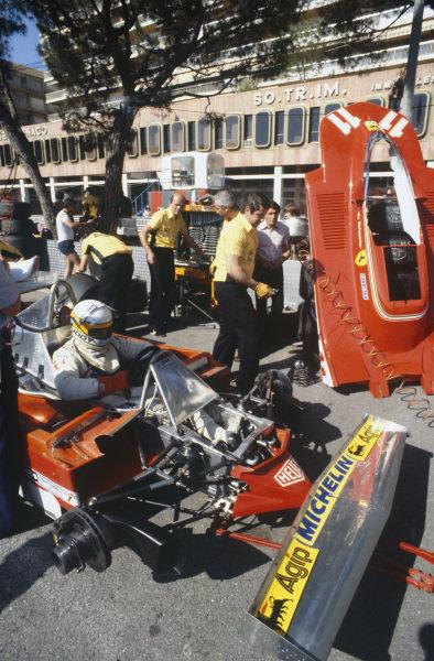 Mechanics work on Jody Scheckter's Ferrari 312T4 as he sits in the cockpit.