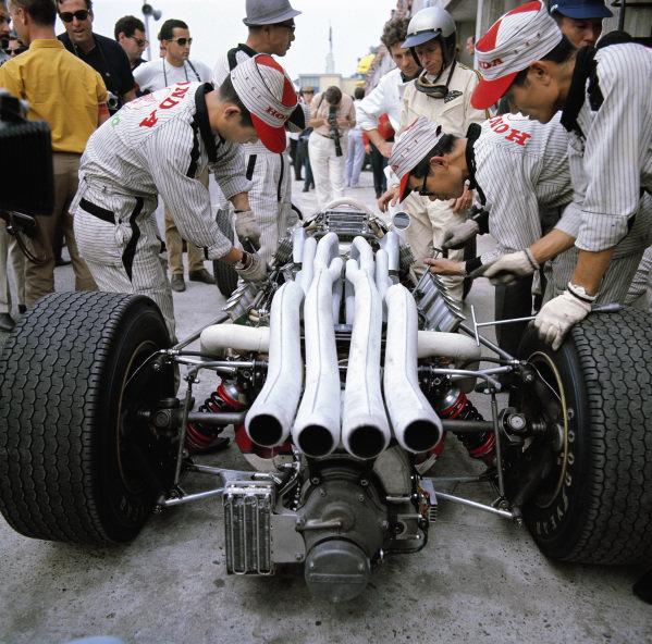 Richie Ginther waits beside his Honda RA273 as mechanics work on the engine.