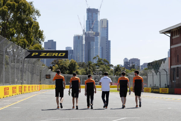 Members of the McLaren team walk the track