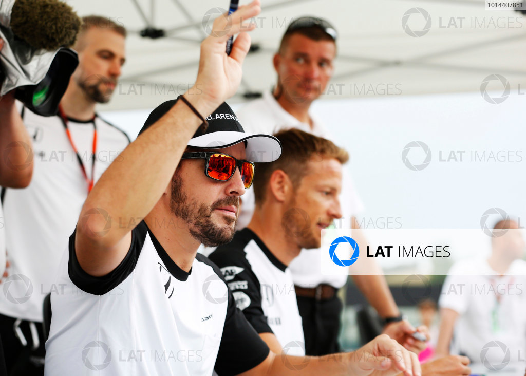 Hungaroring, Budapest, Hungary. Thursday 23 July 2015. Fernando Alonso, McLaren, and Jenson Button, McLaren, sign autographs for fans. World Copyright: Charles Coates/LAT Photographic ref: Digital Image _J5R0929