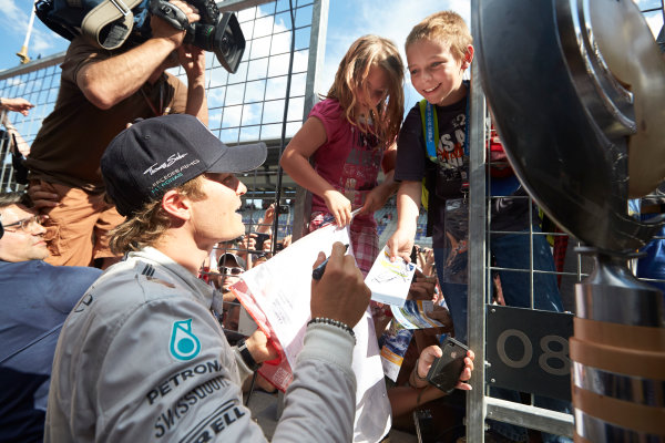 Red Bull Ring, Spielberg, Austria. Sunday 22 June 2014. Nico Rosberg, Mercedes AMG, signs autographs for some young fans. World Copyright: Steve Etherington/LAT Photographic. ref: Digital Image SNE26874copy