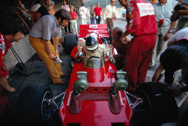Jochen Rindt getting out of his Lotus 72C Ford, watched by Austrian journalist Helmut Zwickl (left), mechanic Herbie Blash (far left) and Colin Chapman (sitting beside the car).