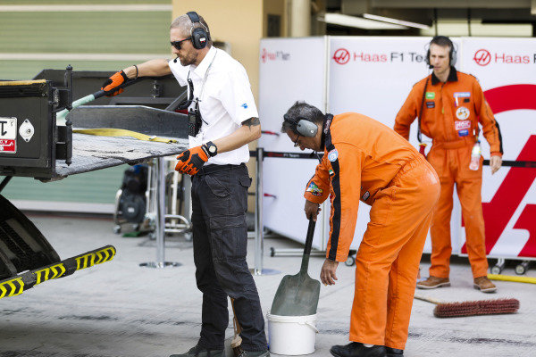 Marshals and Haas team members help return the Pietro Fittipaldi Haas F1 Team VF-18 Ferrari to the pits on a truck.