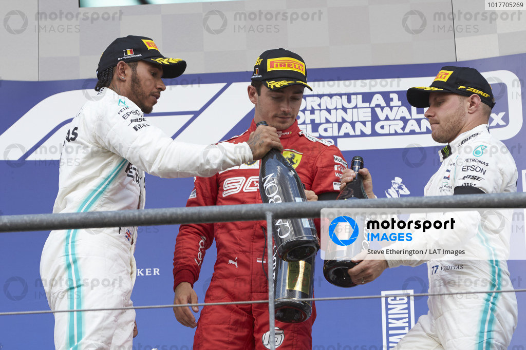 Lewis Hamilton, Mercedes AMG F1, 2nd position, Charles Leclerc, Ferrari, 1st position, and Valtteri Bottas, Mercedes AMG F1, 3rd position, click Champagne bottles on the podium
