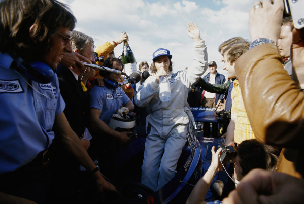 Jackie Stewart, Tyrrell 006 Ford, celebrates in parc ferme after winning.