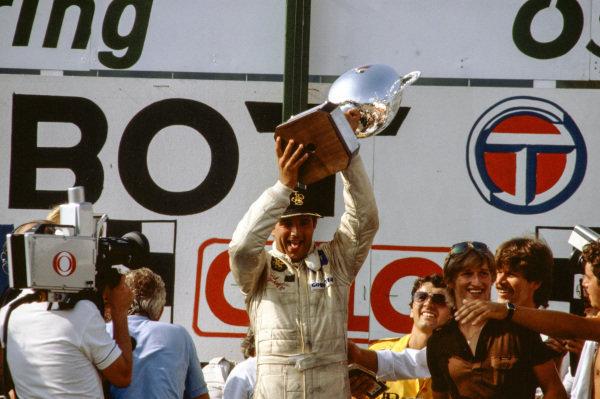 Elio de Angelis, 1st position, raises his trophy on the podium.