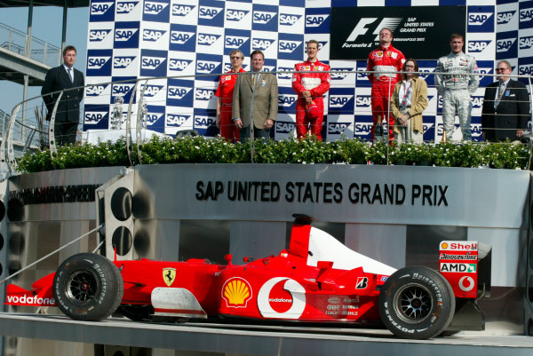 2002 American Grand Prix.Indianapolis, Indiana, USA. 27-29 September 2002.Paolo Martinelli, Michael Schumacher (Ferrari) 2nd position, Rubens Barrichello (Ferrari) 1st position and David Coulthard (McLaren Mercedes) 3rd position on the podium, with the winning car on a platform below.World Copyright - LAT Photographicref: Digital File Only