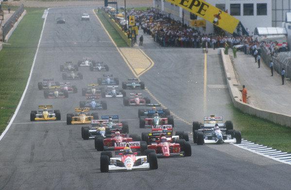 1990 Spanish Grand Prix.Jerez, Spain.28-30 September 1990.Ayrton Senna (McLaren MP4/5B Honda) leads Alain Prost, Nigel Mansell (both Ferrari 641's), Gerhard Berger (McLaren MP4/5B Honda), Jean Alesi (Tyrrell 019 Ford), Riccardo Patrese, Thierry Boutsen (both Williams FW13B Renault's), Alessandro Nannini and Nelson Piquet (both Benetton B190 Ford's) at the start.Ref-90 ESP 14.World Copyright - LAT Photographic
